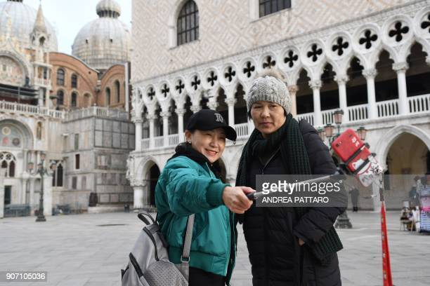 Tourists snap a selfie at Piazza San Marco in Venice on January 19 2018 / AFP PHOTO / Andrea PATTARO