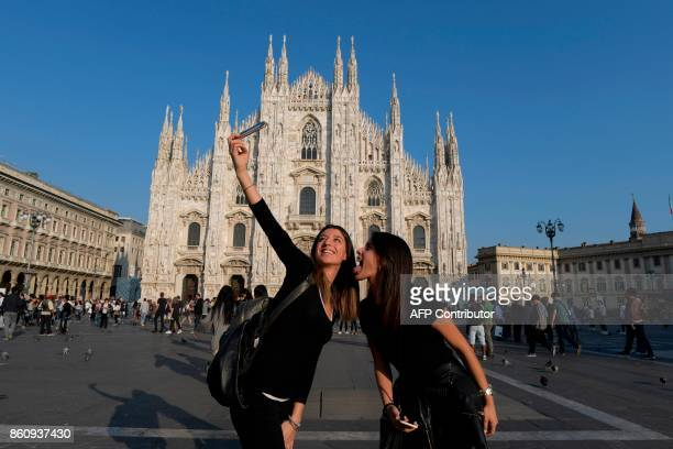 Tourists snap a selfie in front of the Duomo cathedral in Milan on October 13 2017 / AFP PHOTO / MIGUEL MEDINA