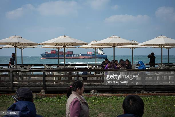 Tourists speculate the damaged cargo ship in a seaside cafe near a coastal area affected by the oil spill near Taiwan's north coast on March 26, 2016...