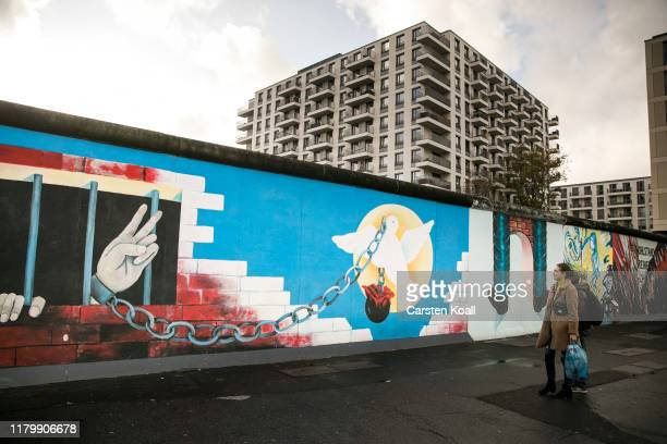 Tourists stand at a former section of the Berlin Wall called the East Side Gallery on the first day of events celebrating the 30th anniversary of the...