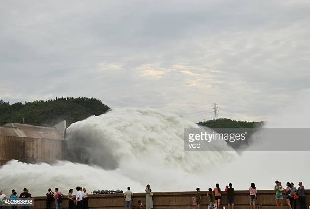 Tourists stand beside a large volume of water transfer at Xiaolangdi Dam on July 3 2014 in Jiyuan Henan province of China