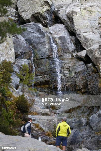 Tourists stand close the nearly dry Cascade des Anglais at the Vizzavona pass on November 1 close from Vivario on the French Mediterranean Island of...