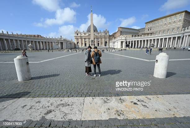 Tourists stand in a deserted St Peter's square at the Vatican on March 6 2020 The Vatican on March 6 reported its first coronavirus case saying it...