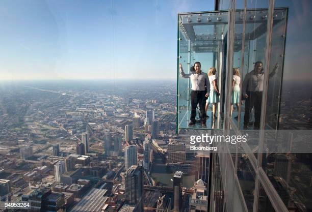 Tourists stand in a glass floored observation deck extending from the 103rd floor of the Willis Tower formerly the Sears Tower in Chicago Illinois US...