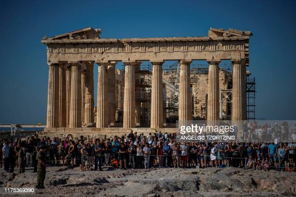 Tourists stand in front the Parthenon temple atop the Acropolis hill during a ceremony marking the anniversary of the liberation of Athens from Nazi...