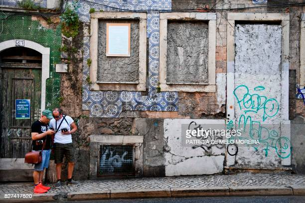Tourists stand is front of a facade covered with typical Portuguese tiles, showing some missing tiles areas, in Lisbon on July 9, 2017. - They used...
