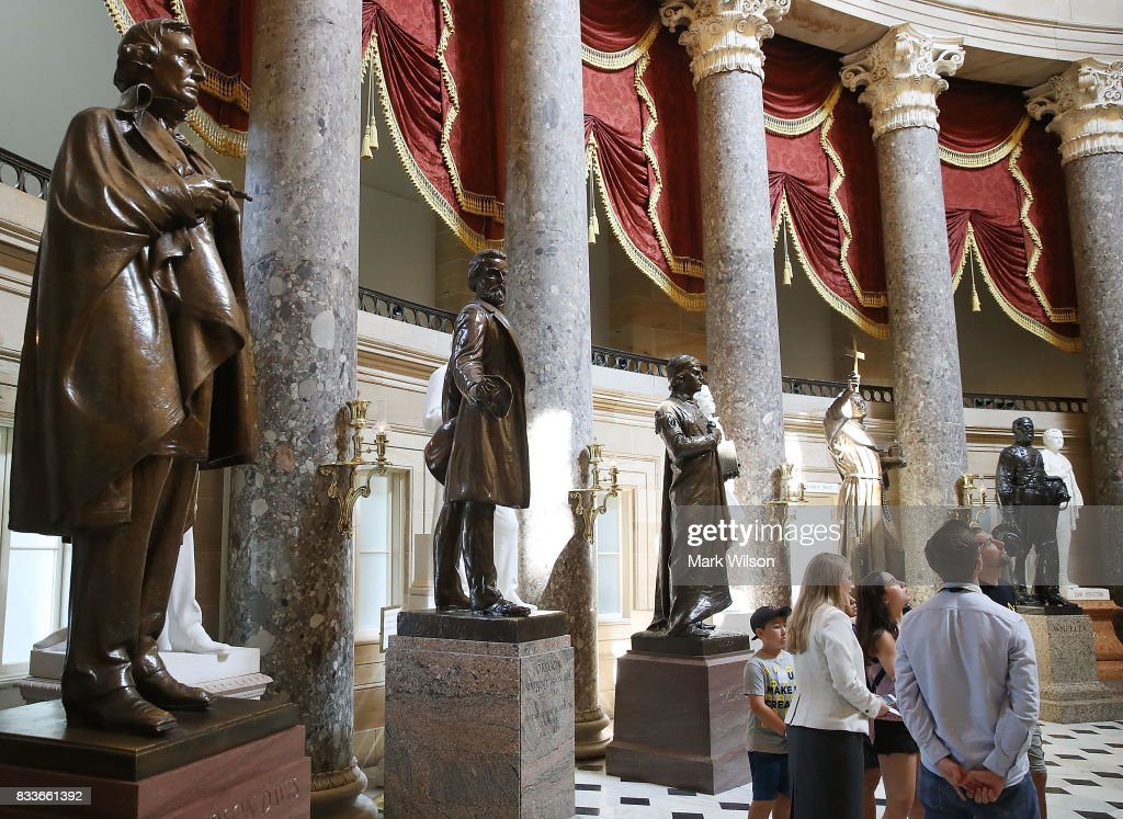 Tourists stand near a bronze statue of Confederate president Jefferson Davis (L) that stands inside of Statuary Hall at the US Capitol August 17, 2017 in Washington, DC. Virginia Governor Terry McAuliffe said he would like to remove all Confederate statues in the wake of a deadly white nationalist rally in Charlottesville.