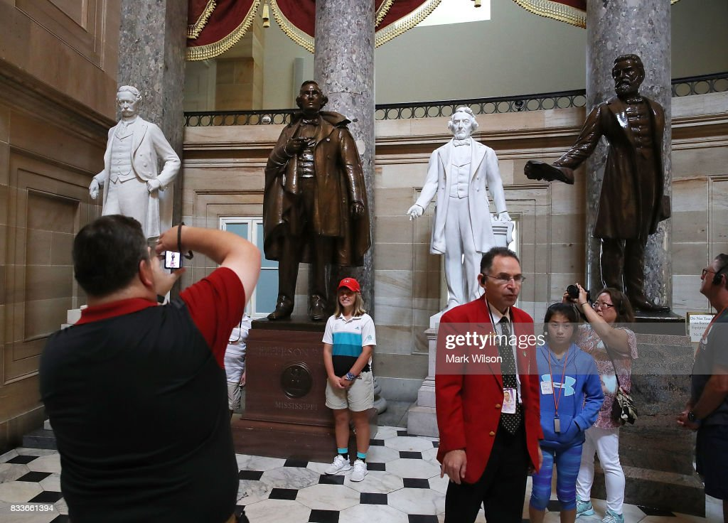 Tourists stand near a bronze statue of Confederate president Jefferson Davis (2ndL) that stands inside of Statuary Hall at the US Capitol August 17, 2017 in Washington, DC. Virginia Governor Terry McAuliffe said he would like to remove all Confederate statues in the wake of a deadly white nationalist rally in Charlottesville.