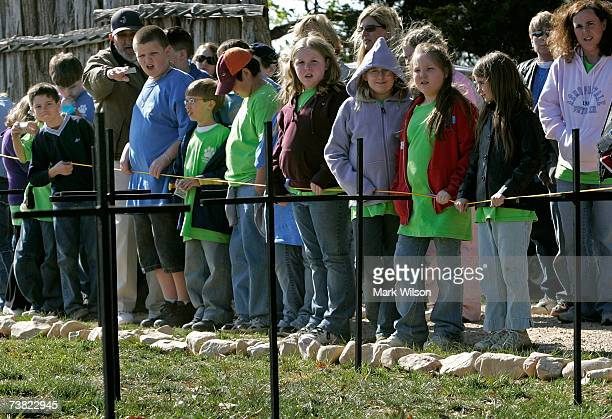 Tourists stand near twentytwo crosses that mark spots where archaeologists with the Association for the Preservation of Virginia Antiquities have...
