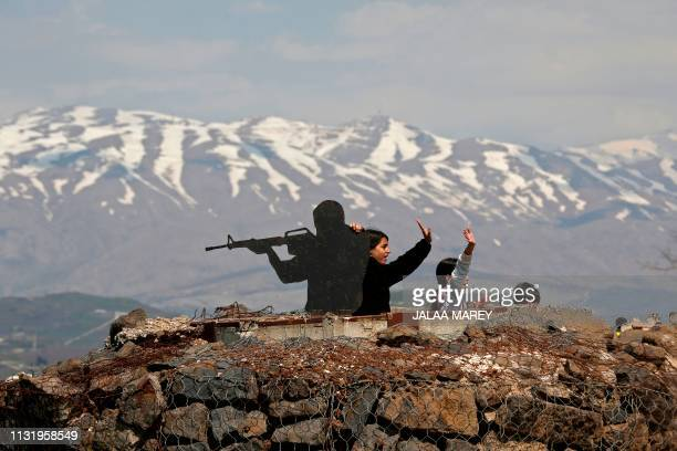 Tourists stand next to a silhouette sculpture of an Israeli soldier at an army post on Mount Bental in the Israeliannexed Golan Heights on March 22...