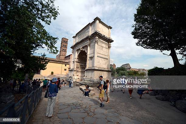 Tourists stand next to the Arch of Titus in the ancient Roman Forum on the Palatine hill in Rome on September 17 2014 AFP PHOTO / FILIPPO MONTEFORTE