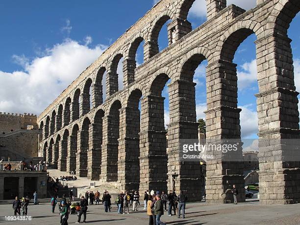 Tourists stand next to the roman aqueduct in Segovia Autonomous Community of Castilla Leon Spain March 2012