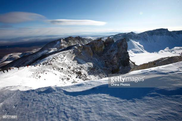 Tourists stand on a hill to view the Tianchi or Heaven Lake on January 11 2010 in Antu County of Yanbian Korean Autonomous Prefecture Jilin Province...