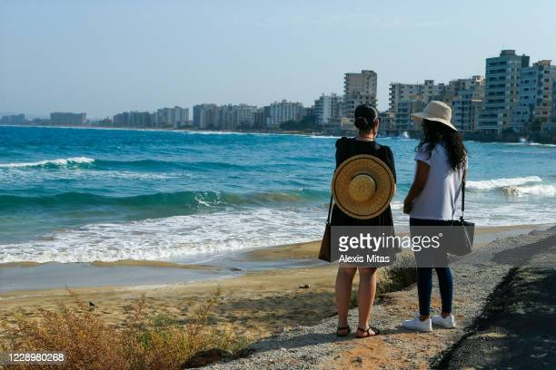 Tourists stand on a newly opened beach on October 9, 2020 in the disputed coastal town of Varosha in Famagusta, Cyprus. The controversial reopening...