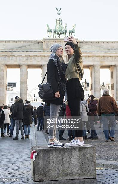 Tourists stand on a recently installed cement block to take a selfie in front of the capital's Brandenburg Gate on December 31 2016 Security has been...