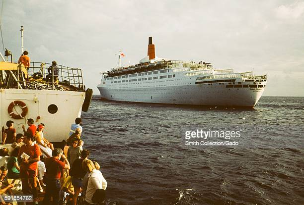 Tourists stand on a small boat as it approaches Cunard Line's Queen Elizabeth 2 cruise ship at sea 1975