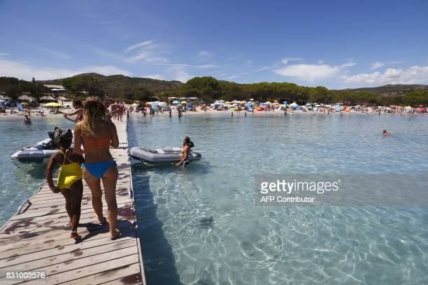 Tourists stand on Rondinaria beach close from Bonifacio on the French Mediteeranean island of Corsica on August 13 2017 / AFP PHOTO / PASCAL...