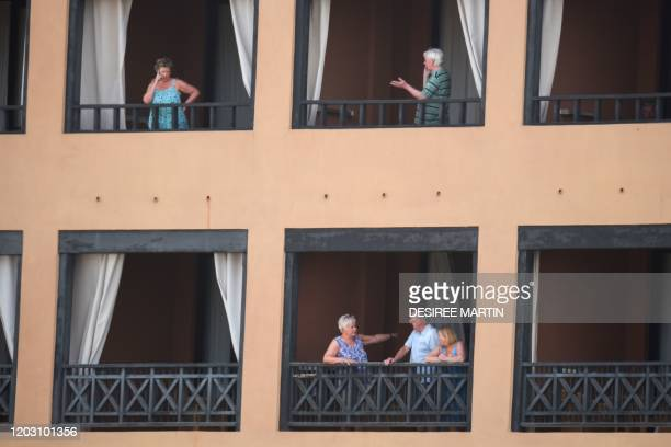 Tourists stand on the balconies of their rooms at the H10 Costa Adeje Palace Hotel in La Caleta, on February 25 where hundreds of people were...