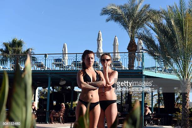 Tourists stand on the beach at the Bella Vista Hotel in Egypt's Red Sea resort of Hurghada on January 9 the day after the hotel came under attack by...