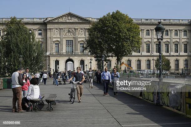 Tourists stand on the Pont des Arts with its railings covered by padlocks on September 23 2014 in Paris Paris officials have put up long panels on...