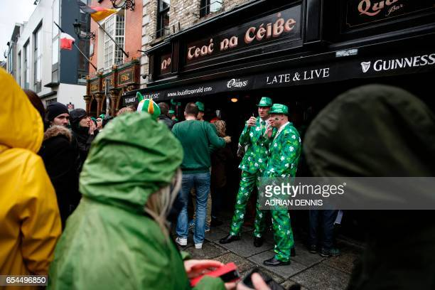 Tourists stand outside a pub in Temple Bar during the St Patrick's Day parade in Dublin Ireland on March 17 2017 / AFP PHOTO / ADRIAN DENNIS