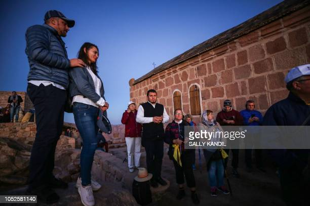 Tourists stand to watch the sunrise after scaling Mount Catherine above the 6thcentury Greek Orthodox Christian monastery of Saint Catherine near the...