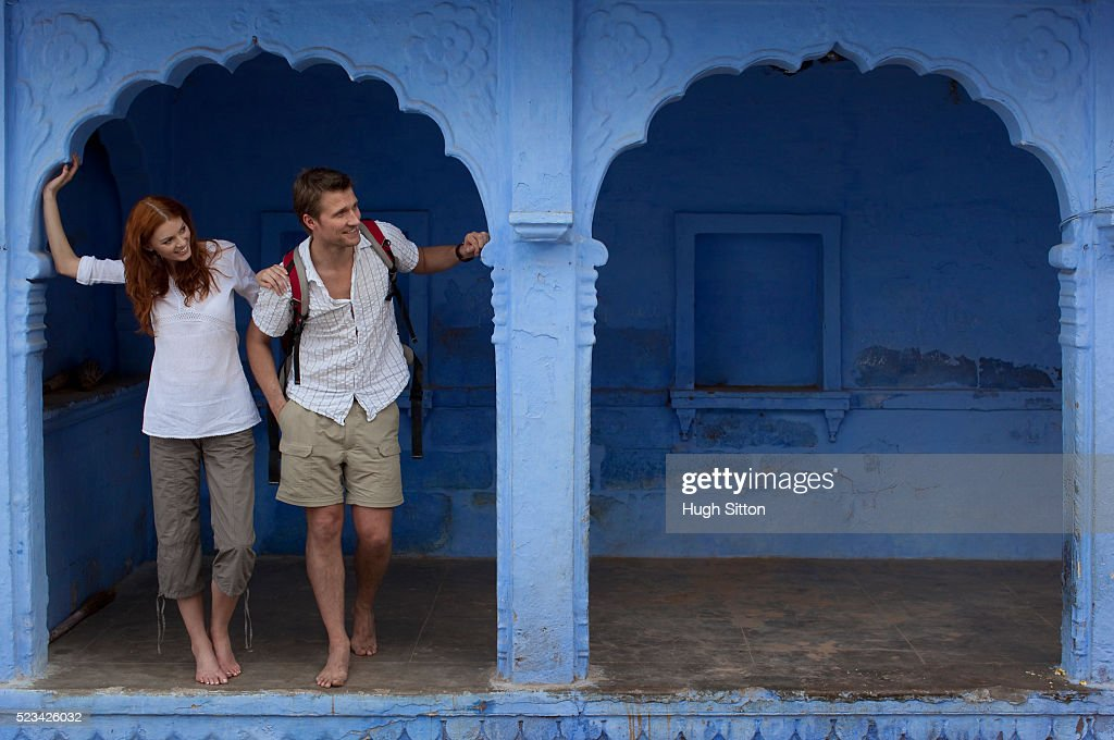 Tourists standing in archway of blue building : Stock Photo