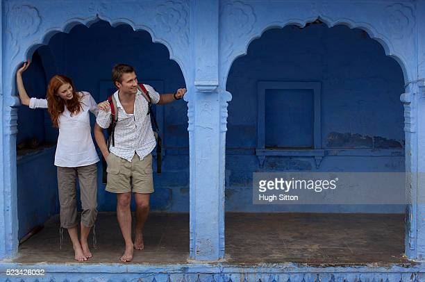 tourists standing in archway of blue building - hugh sitton stockfoto's en -beelden