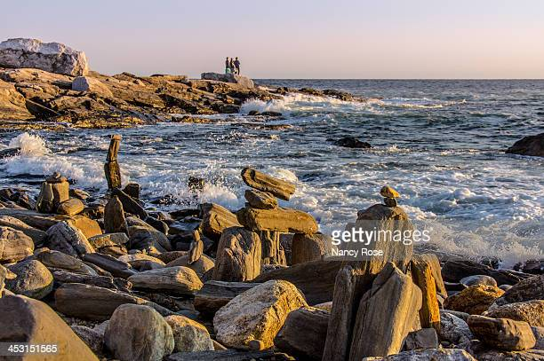 CONTENT] Tourists standing on rocky point watching waves at Pemaquid Point in Maine