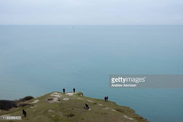 Tourists standing on the edge of the White Cliffs of Dover, Kent. One of the most famous and iconic landmarks of Britain. They face the straights of...