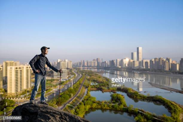 tourists standing on the rocks overlooking the city - fuzhou stock pictures, royalty-free photos & images