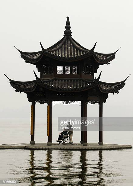 Tourists stay at a pavilion on an island of the West Lake on April 19 2005 in Hangzhou of Zhejiang Province east China The West Lake covering 65...