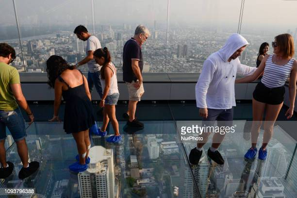 Tourists step on the glass skywalk on the 78th floor of the King Power Mahanakhon skyscraper highest observation deck, in Bangkok, Thailand, 04...