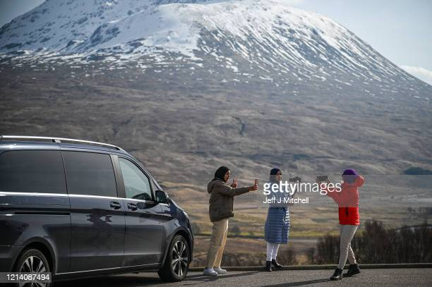 Tourists stop for a photograph in Glen Coe as members of the public are asked to stop traveling to the Scottish Highlands in a bid to avoid spreading...