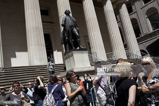 Tourists stop on Wall Street in front of Federal Hall and a statue of George Washington June 8 2012 across from the New York Stock Exchange in New...