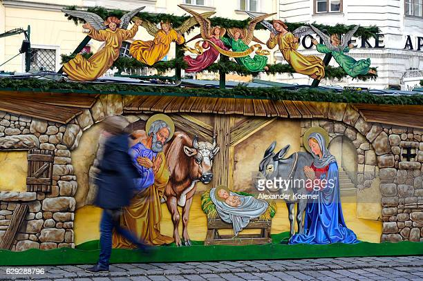 Tourists stroll along a painting showing the birth of Jesus Christ at a christmas market on December 5 2016 in Vienna Austria The town of Vienna is...
