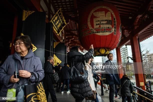 Tourists stroll beneath a huge lantern in Sensoji buddhist temple on January 19 2018 in Tokyo Japan Sensoji is Tokyo's oldest temple dating back to...