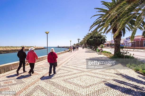 Tourists strolling along Promenade, Lagos, Portugal