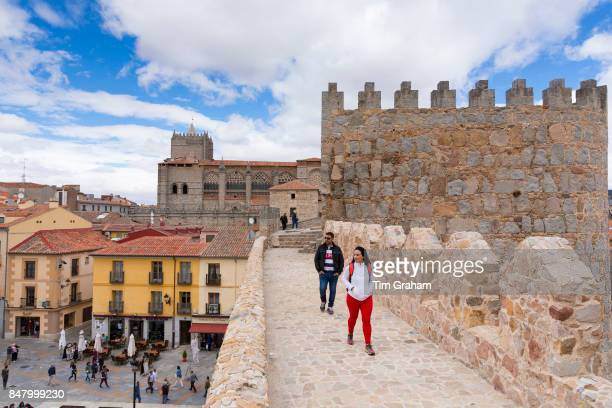Tourists strolling along the top of the medieval city wall in Avila Spain