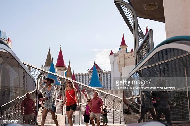 Tourists strolling on footbridge in front of fairytale castle hotel, Las Vegas, Nevada, USA