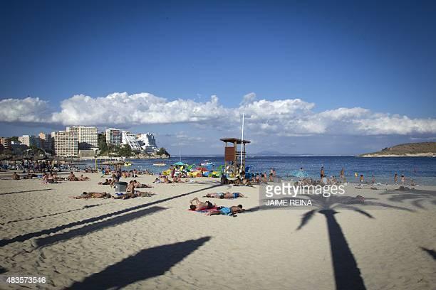 Tourists sunbath at Magaluf's beach in Calvia on Mallorca Island on August 10 2015 AFP PHOTO/ JAIME REINA