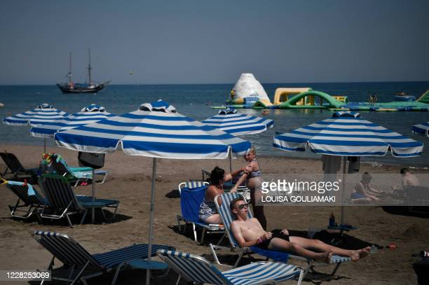 Tourists sunbath on the beach at Faliraki Bay in the Aegean island of Rhodes on August 29, 2020. - Rhodes island, one of the mass tourism Greek...