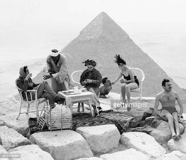 Tourists sunbathe and take tea at the top of the Great Pyramid