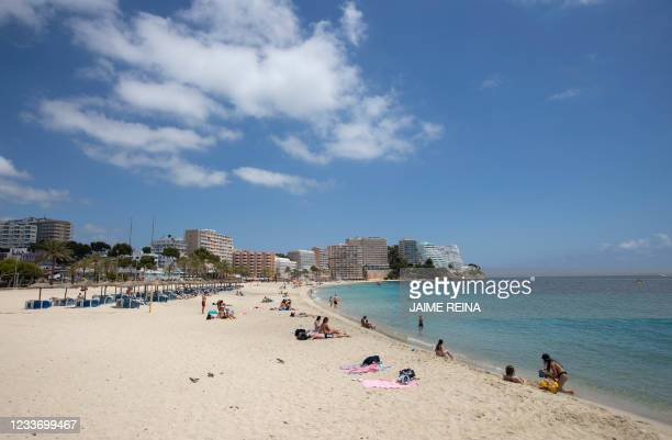 Tourists sunbathe at Magaluf Beach in Calvia, on the Balearic Island of Mallorca, on June 28, 2021. - British holidaymakers heading to the Balearic...