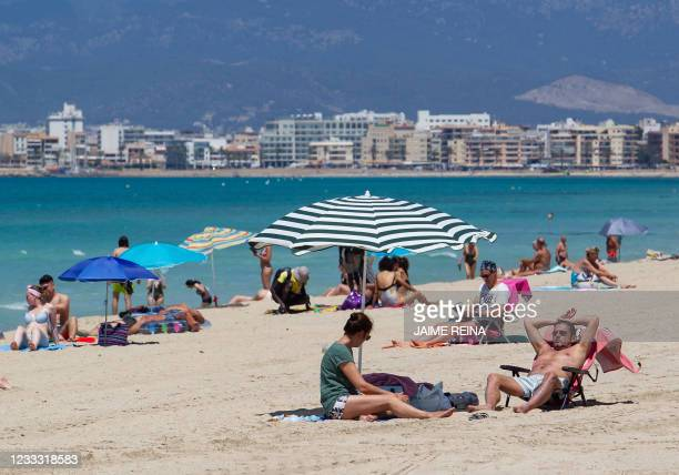 Tourists sunbathe at Palma Beach in Palma de Mallorca on June 7, 2021. - Spain opened its borders to vaccinated travellers from all over the world,...