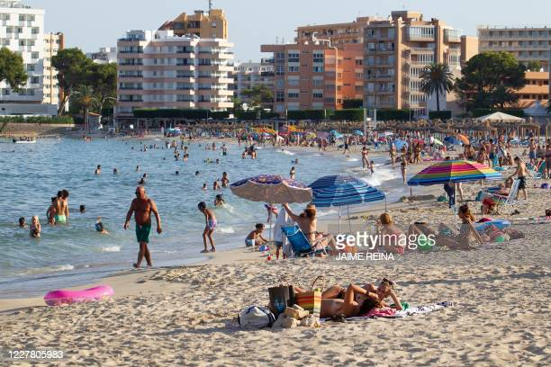 Tourists sunbathe at Palmanova Beach on the Island of Mallorca on July 27, 2020. - Tour operator TUI has cancelled all British holidays to mainland...