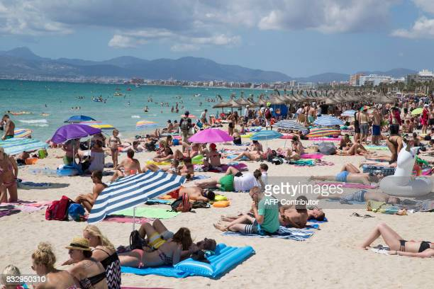 Tourists sunbathe at Playa de Palma in Palma de Mallorca on August 12 2017 Known as much as a wild party island as a place of tranquility with coves...