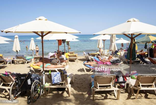 Tourists sunbathe on a beach opposite Cactus hotel in Hersonissos, on the island of Crete, Greece, on Tuesday, Sept. 24, 2019. Like Crete, Europes...