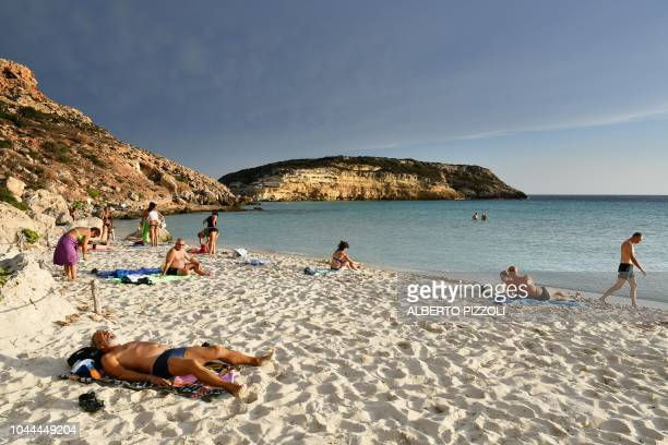 Tourists sunbathe on the beach of the Isola dei Conigli in Lampedusa on September 25 2018 Five years after the worst shipwreck of its history the...