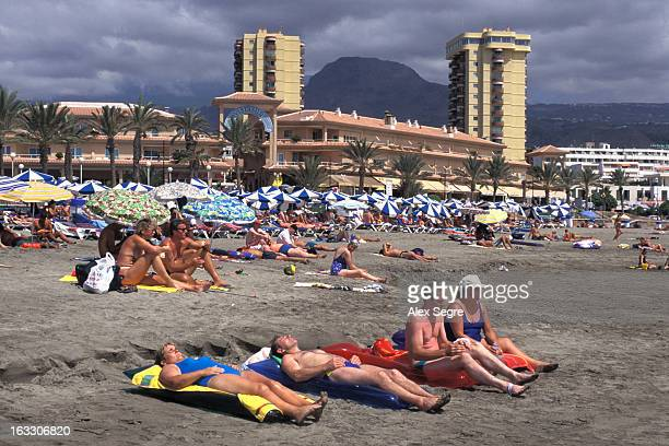 Tourists sunbathing on the beach at Playa de las Americas
